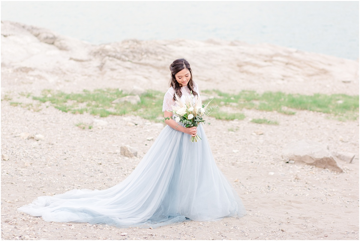 bride for their engagement session with light rock with dusty blue skirt holding a bouquet with bunny tail and greenery made by the willow flower co