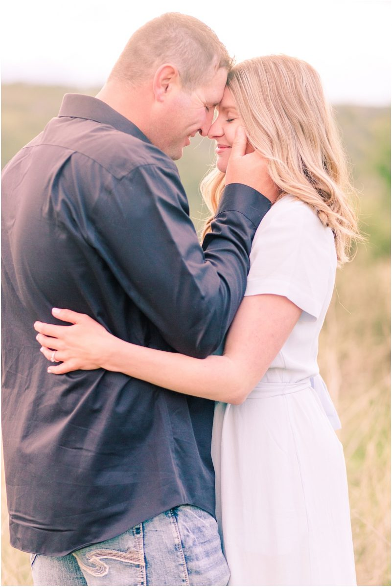 alebrta light and airy photographer engagement photos in alberta near fairview at dunvegan with sunset and glowy light in the background very romantic photo