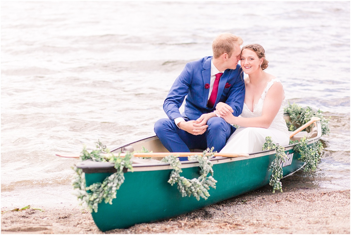 shelbee and danial in the green canoe at grande cache lake in the mountain banff jasper for their wedding photos