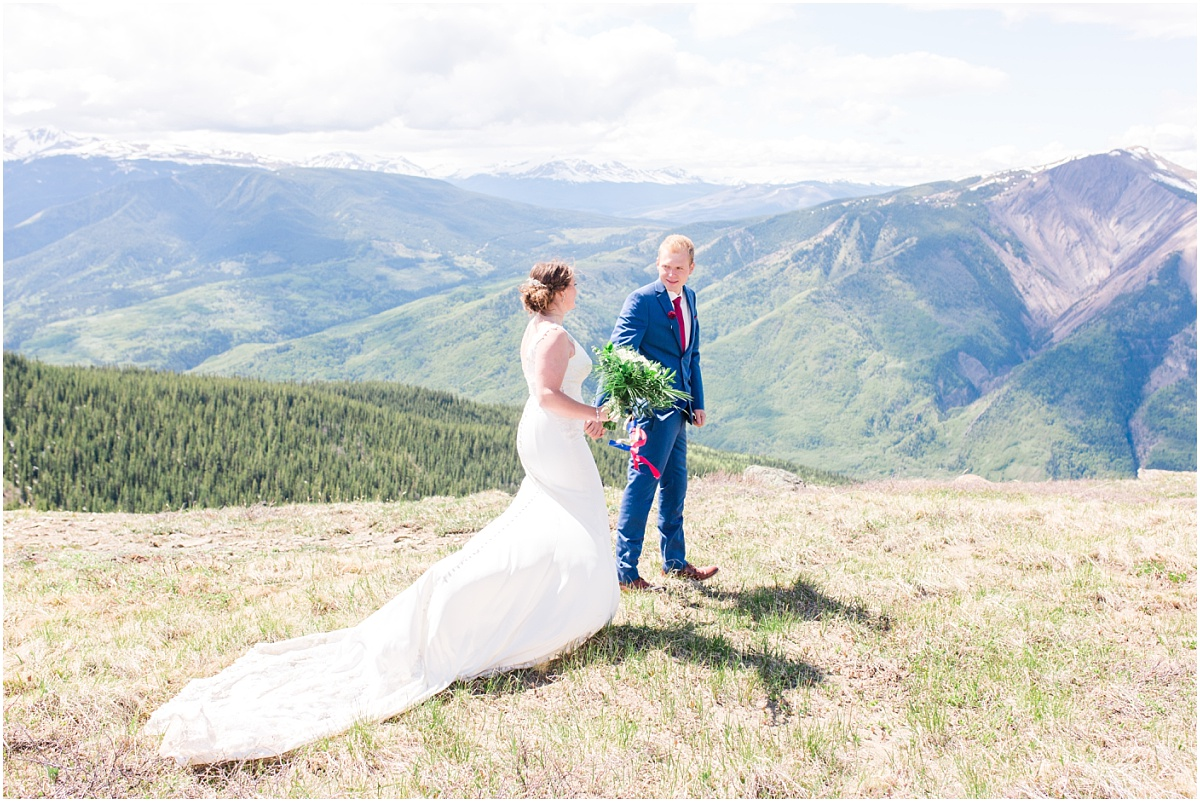 bride and groom walking with mountain view for their wedding photos with grande cache mountain holding hands