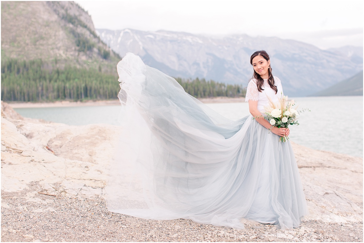blue tulle skirt with canadian rocky mountains bride and her engagement photos flying in the air dress shot photos
