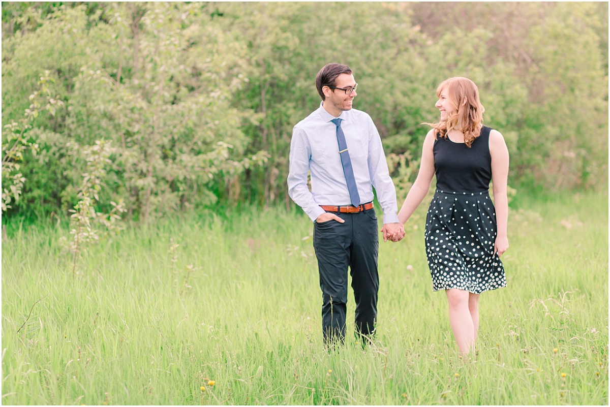 fiance walking holding hands for their engagement photos with trees in the background walking in tall grass with a very light and airy style located in grande prairie at the park