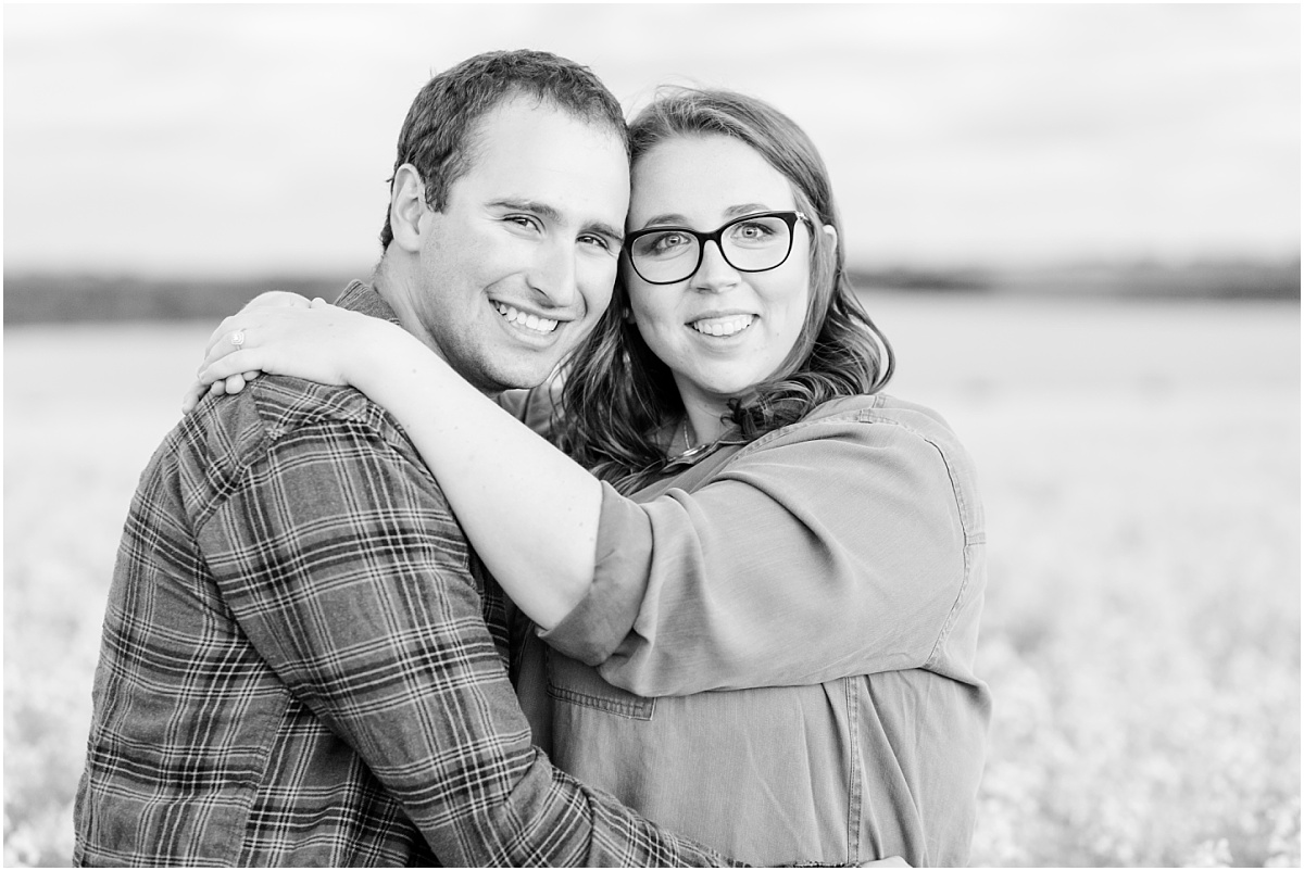 camille and justin smiling for their canola field grande prairie engagement session photos with kayla lynn photography