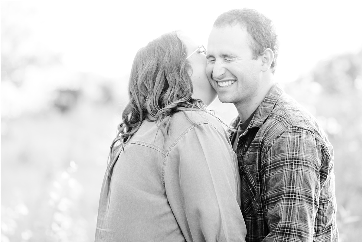 whisper in ear candid smiles in the alberta engagement session for justin and Camille black and white photo full of emotion