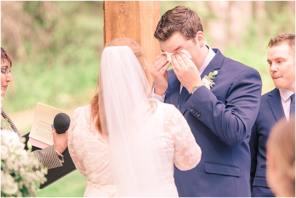 groom crying during the covid wedding ceremony very emotional in grande prairie backyard elegant wedding