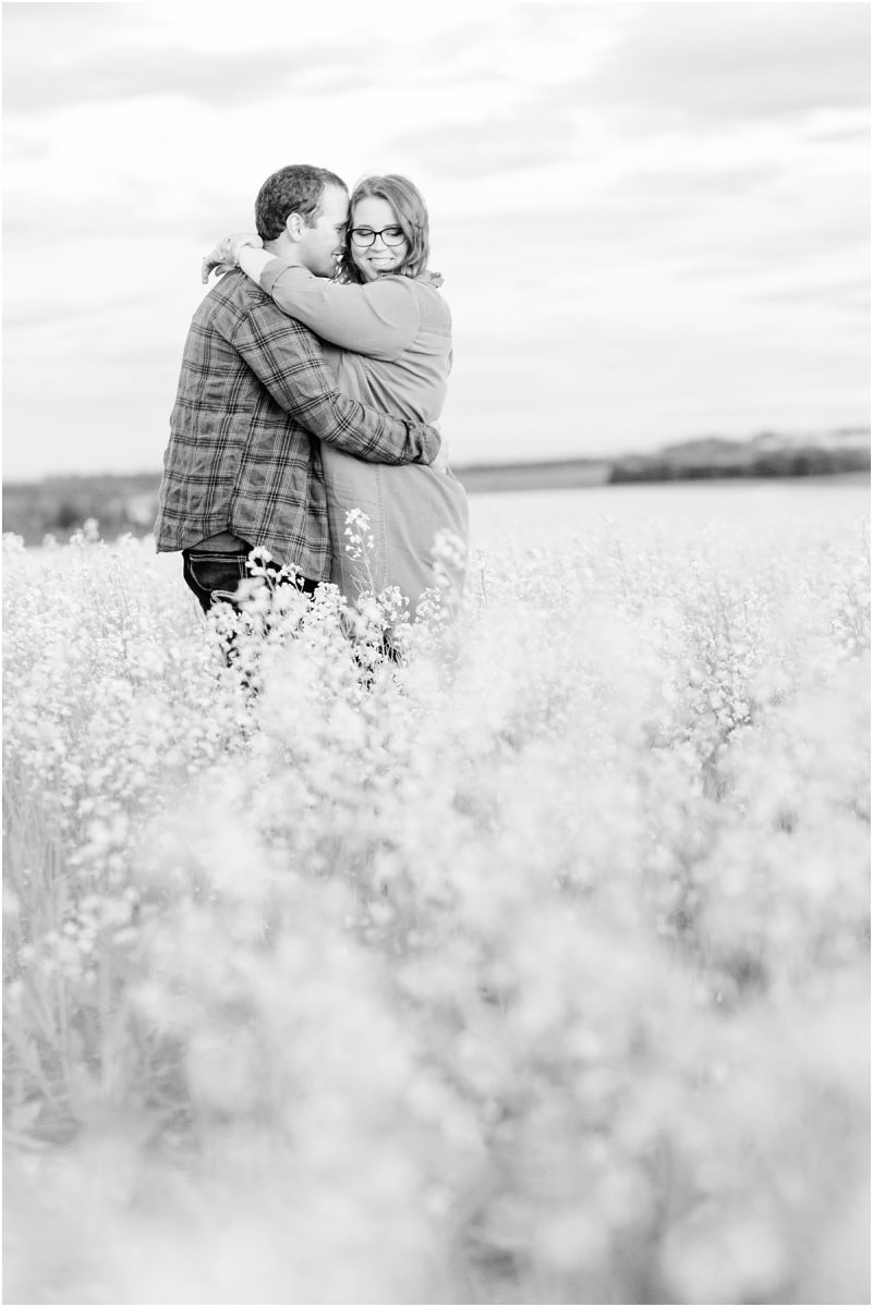 black and white grande prairie alberta engagement photo in the canola field with justin and camille casual plaid clothing