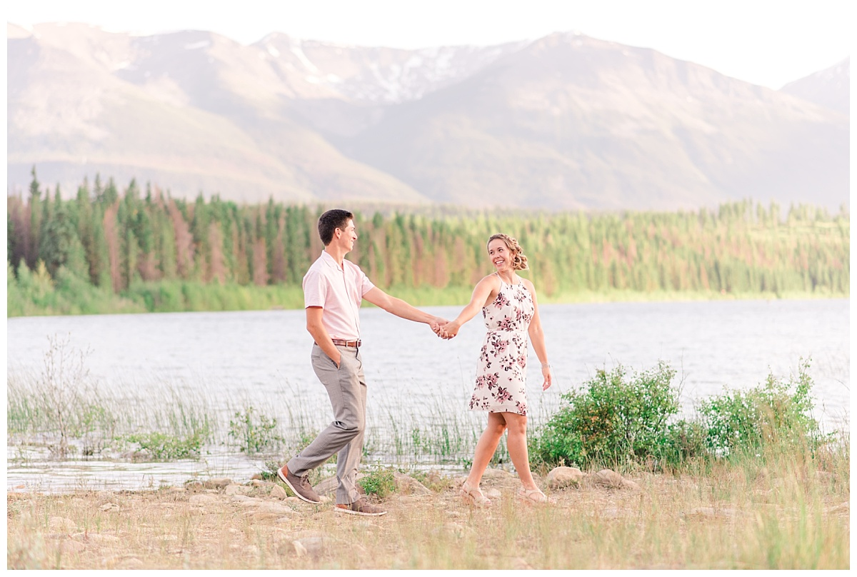 walking photo with light and airy jasper alberta photographer with mountains in the background wearing floral dress formal