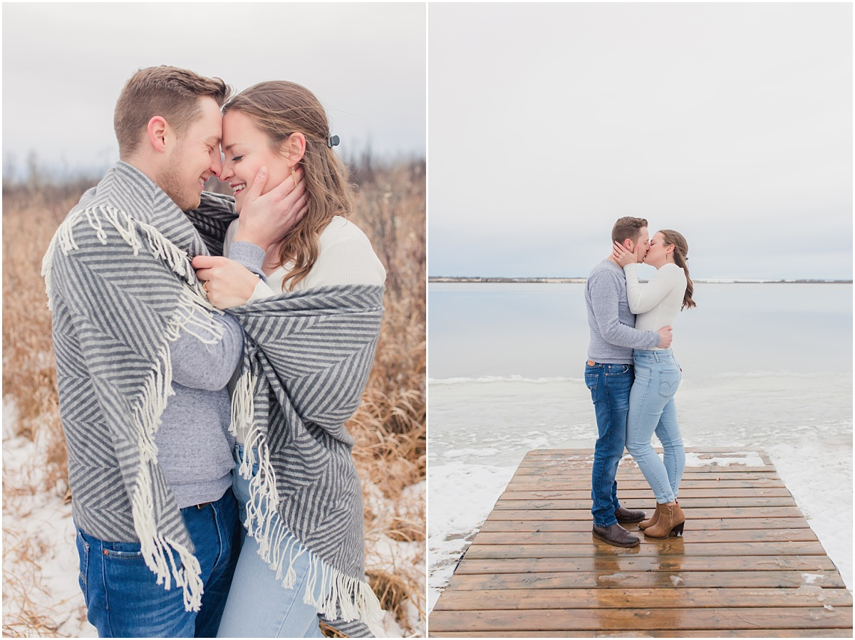 couple engagement photos at saskatoon island lake provincial park on the dog kissing and wrapped in a blanket with stripes