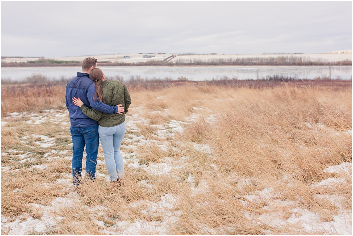 couple looking at saskatoon island lake in alberta where brodie first proposed to her in grande prairie