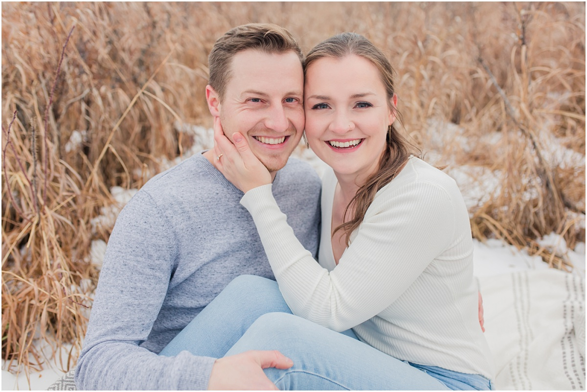shailene and brodie smilig at the camera light and airy wedding photography style captured in grande prairie alberta in the light golden grass for sitting photos