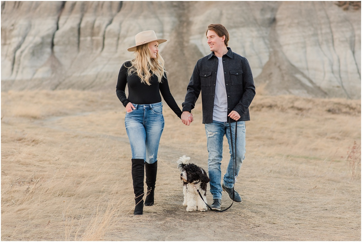dog engagement photos with photogrpaher in grande prairie walking with their dog with kleskun hills in the background wide shot