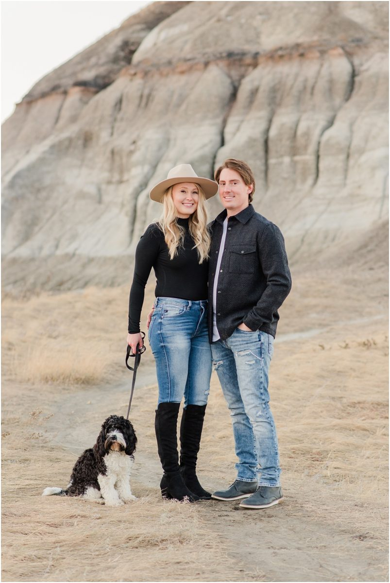 engagement photos fulll body shot with their dog willa black and jeans clothing at klesun hills with golden grass in the background and sandy hills