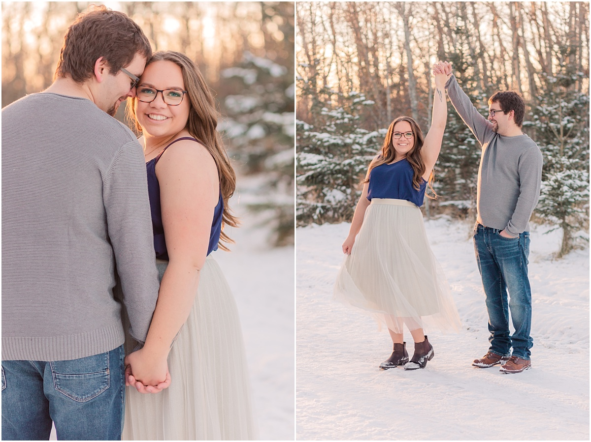 damon twirling deanna for their winter engagement photos with snow wearing purple top and jeans with spruce trees in the background very beautiful photos in grande prairie on the crystal lake path