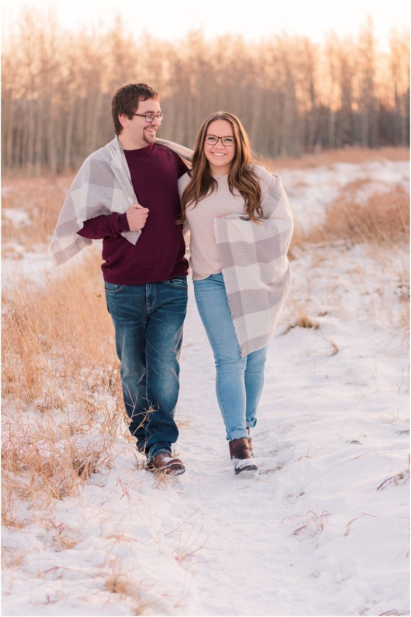 damon and deanna walking in grande prairie crystal lake walking with grey blanket wrapped around them smiling during golden hour in grande prairie