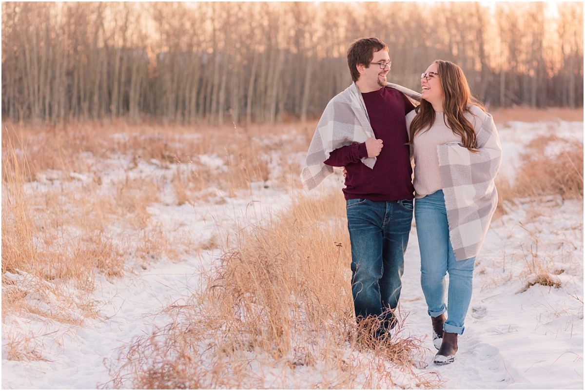 couple walking in field with light grass and snow in crystal lake grande prairie with grey blanket wrapped around them wearing burgundy shirt and jeans