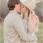 signature photo of zach and laura kissing close up holding tan hat from the headroom the stripped dress kissing very light and airy and romantic photo