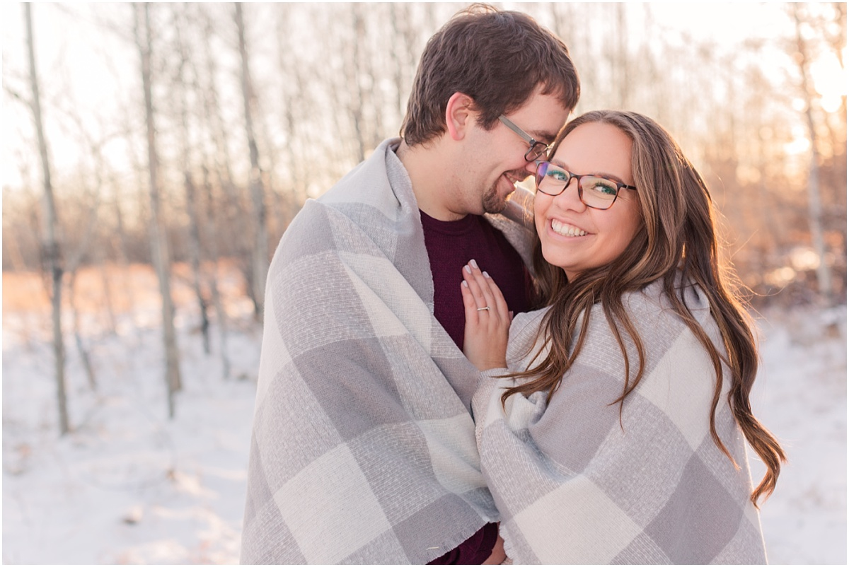 damon and deanna wrapped around blanket for their winter snow engagement photos in grande prairie alberta in crystal lake with sunset in the background and trees