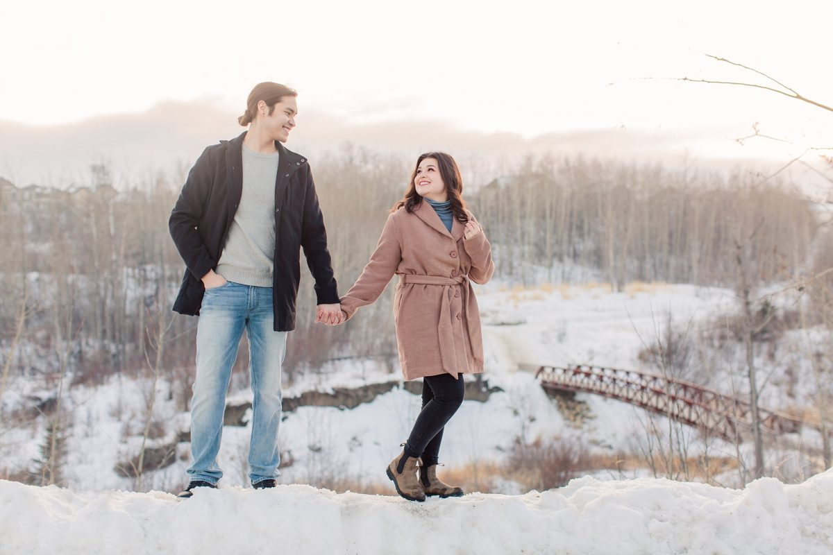 beautiful wide shot winter engagement photo in grande prairie couple emma and darrion holding hands bridge in the background