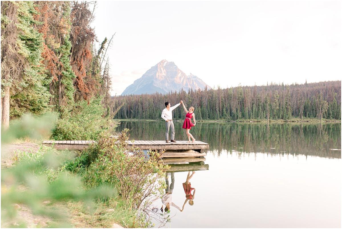 couple twirling photos wearing red dress wide shot at leech lake in jasper
