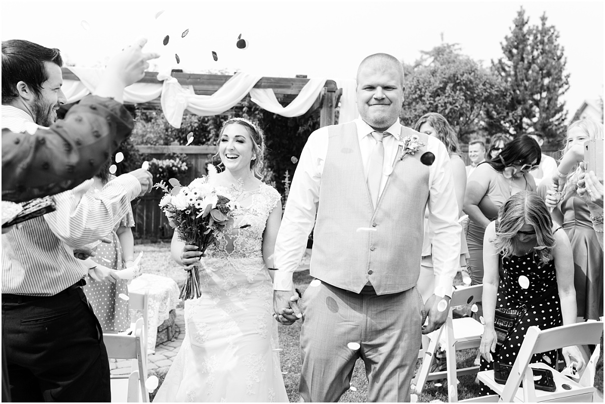 fun confetti close up photo bride and groom walking down the aisle happy they are married
