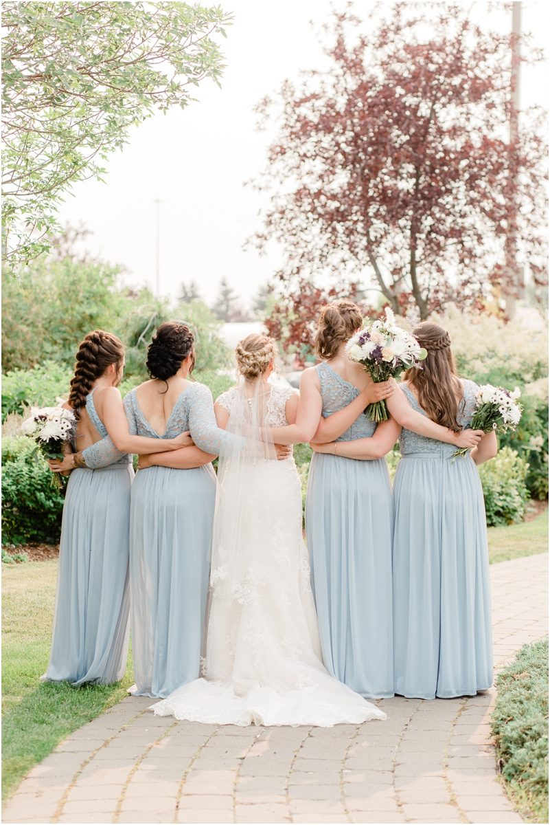 bridemaids back arms around each other dusty blue dresses