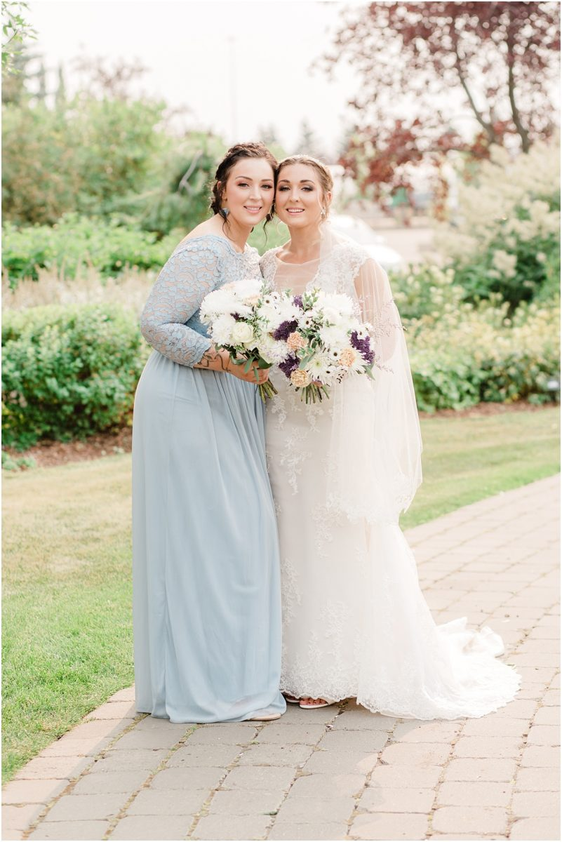 bride with her sister maid of honor wearing dusty blue dress happy sisters