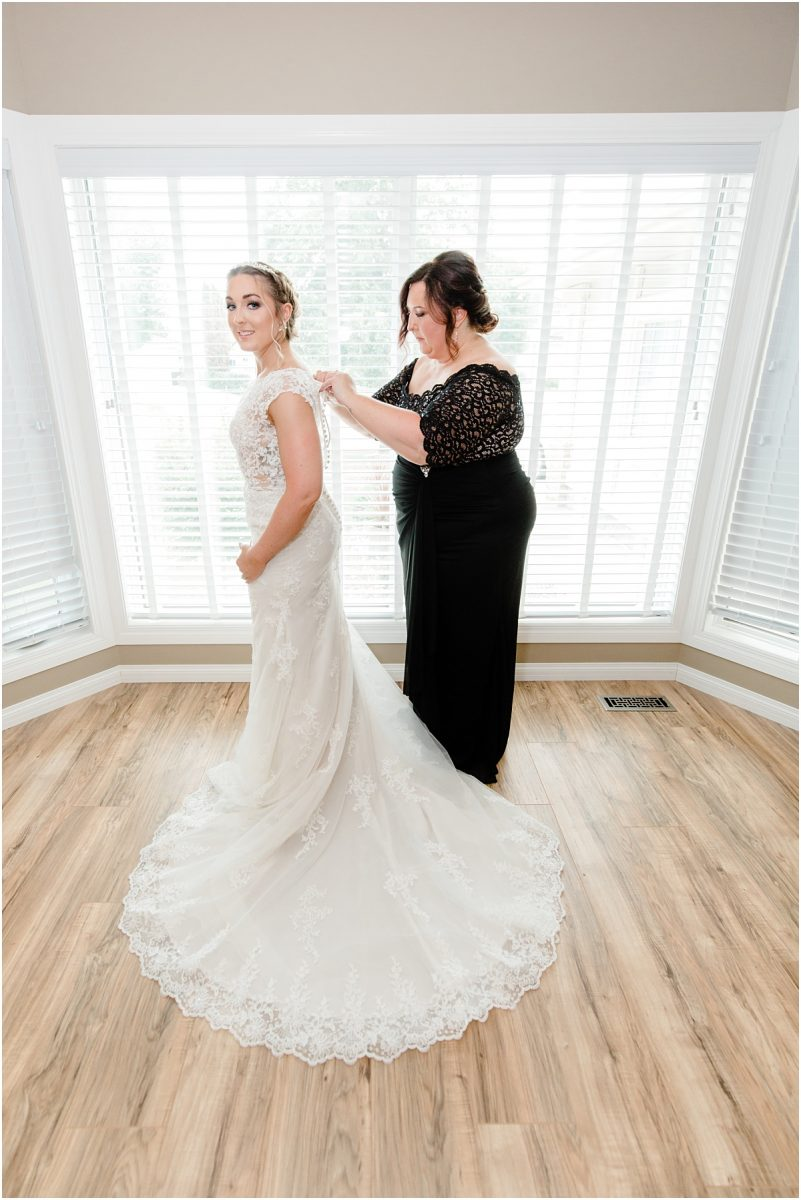 mother of the bride getting ready photos putting on the dress