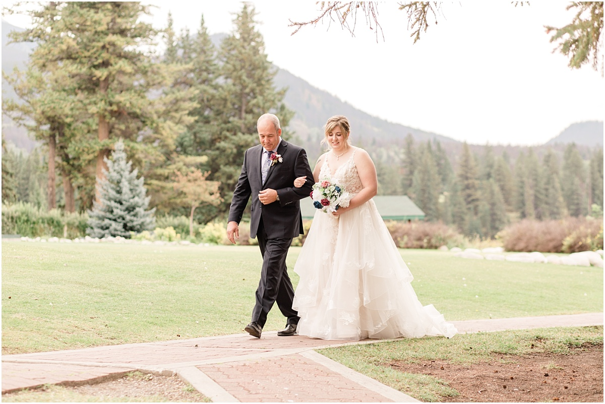 daddy daughter walking down the aisle with jasper mountains in the background