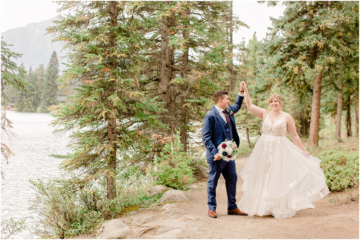 groom twirling his bride in jasper for their wedding photos in the spruce trees wedding photos with light and airy style