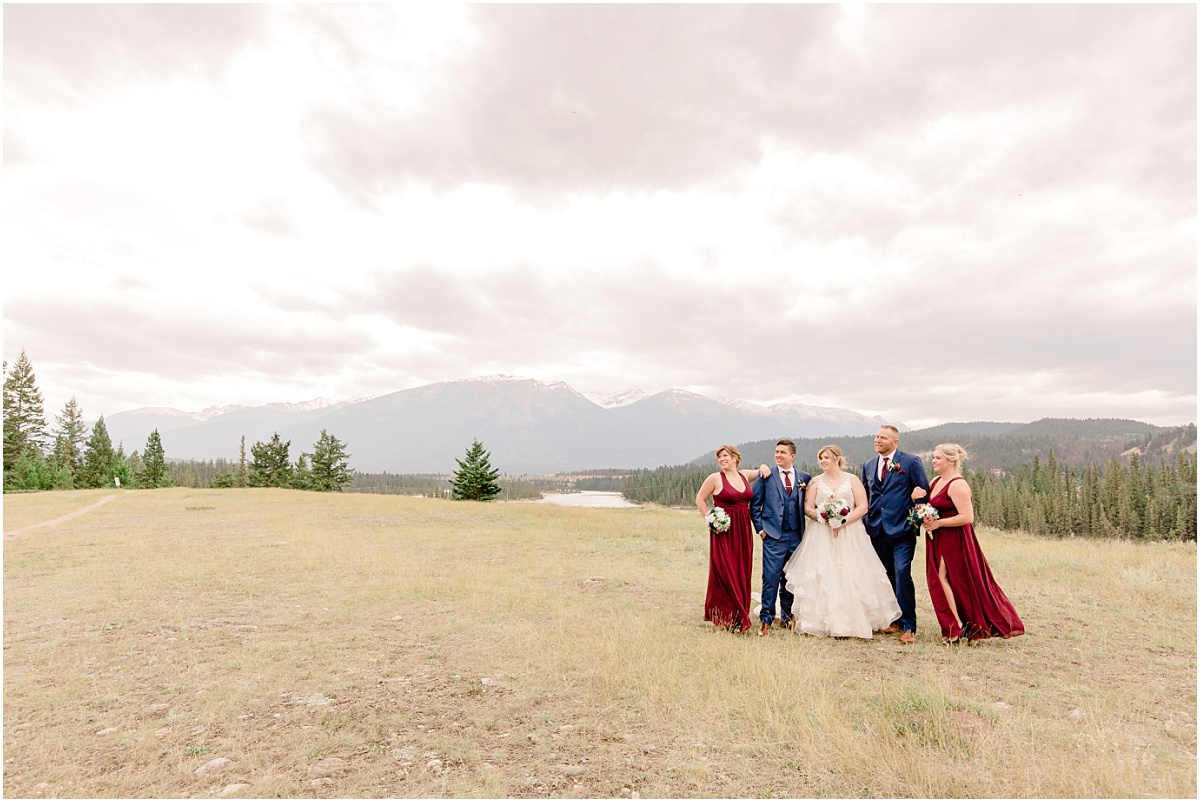 bridal party photos in jasper with the vest views mountains in the background wide shot with the moody clouds