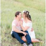 grande cache wedding photographer doing photos of romantic couple sitting down at kleskun hills in the grass with hills in the background